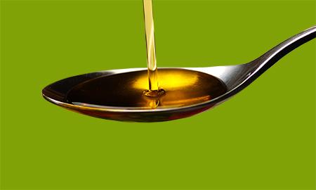 Olivenoel fließt in einen Loeffel